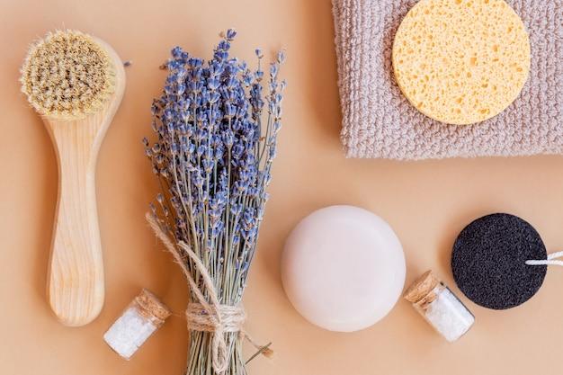 ホームスパ用オーガニック化粧品のセットです。ベージュの背景に天然毛、石鹸バー、海塩、スポンジ、タオルを使ったフェイスマッサージブラシ。上面図