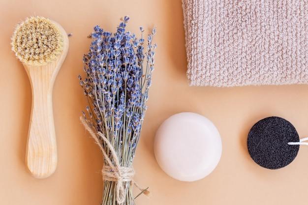 Набор органической косметики для домашнего спа. кисточка для массажа лица с натуральной щетиной, куском мыла, губкой и полотенцем на бежевом фоне. вид сверху.