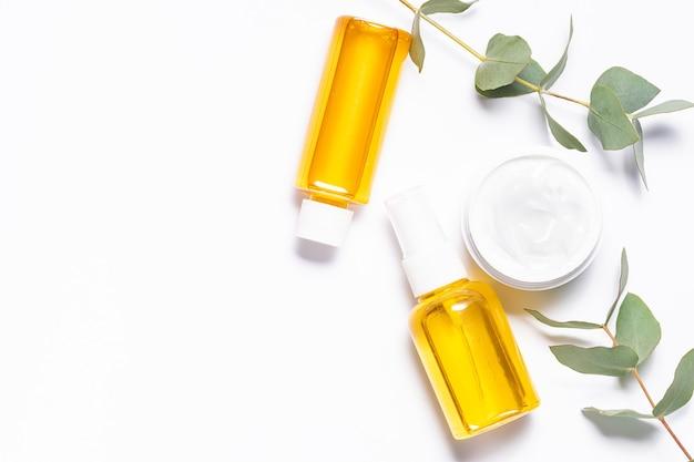有機エッセンシャルオイルと白い背景の上の新鮮な芳香のユーカリの葉のセット