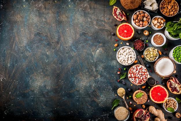有機健康ダイエット食品、スーパーフード-豆、マメ科植物、ナッツ、種子、緑、果物、野菜のセット。暗い青色の背景コピースペーストップビュー