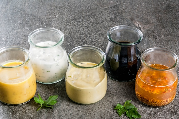サラダ用の有機健康食用ドレッシングのセット:ソースのビネグレット、マスタード、スパイスまたは牧場のマヨネーズ、バルサミコ酢または大豆、ヨーグルトのバジル。暗い石のテーブルの上。コピースペース