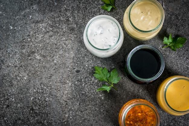 サラダ用の有機健康食用ドレッシングのセット:ソースのビネグレット、マスタード、スパイスまたは牧場のマヨネーズ、バルサミコ酢または大豆、ヨーグルトのバジル。暗い石のテーブルの上。トップビューコピースペース