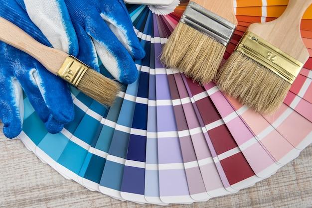 컬러 용지 팔레트 가이드, 파란색 장갑 및 나무 보드에 브러시로 페인트 도구 세트