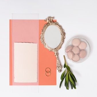 Set of papers near macaroons on plate, rings and mirror