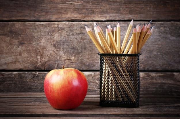 Набор карандашей в металлическом держателе и свежее яблоко на деревянном фоне
