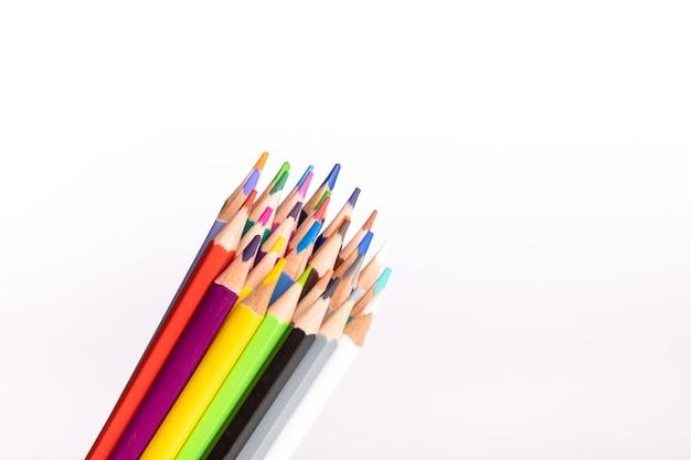 白い背景の上のさまざまな色の鉛筆のセットバックスクール