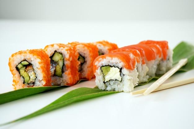 Набор суши филадельфия и калифорния на зеленом листе с деревянными палочками. традиционная японская кухня.
