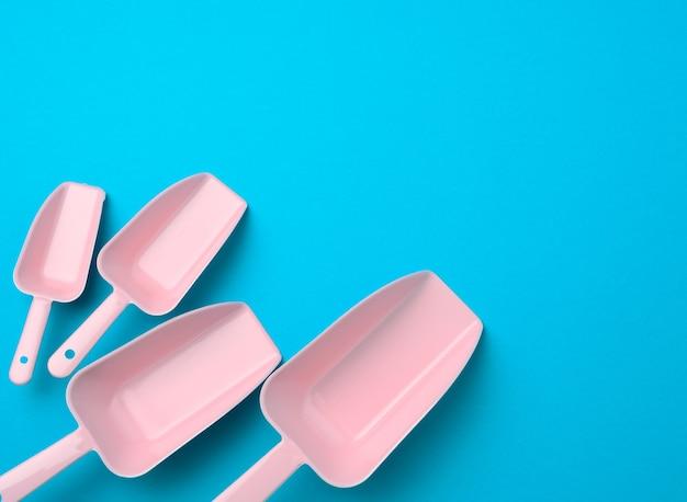 Набор розовых пластиковых кухонных совков для сыпучих продуктов на синем фоне, плоская планировка