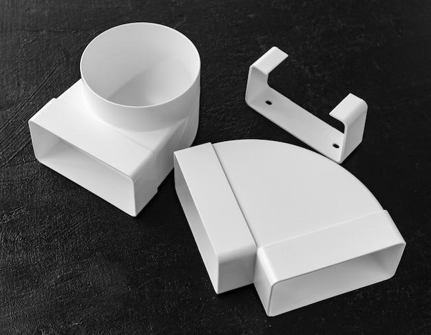 부엌에서 환기, 공기 덕트 또는 후드를 조립하기 위한 플라스틱 부품 세트. 검정색 배경
