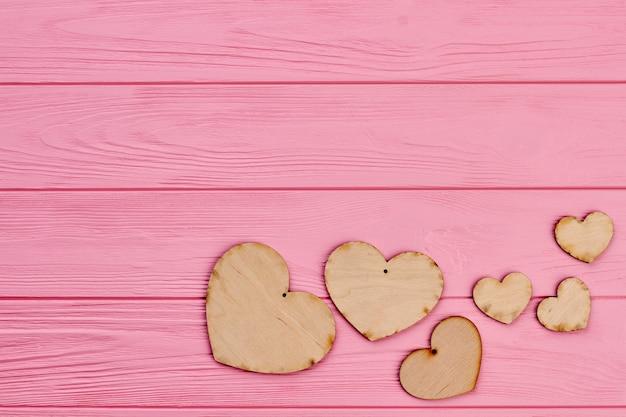 합판 하트와 복사 공간의 집합입니다. 핑크 나무 배경에 나무로 만든 갈색 소박한 마음. 발렌타인 데이 나무 배경입니다.