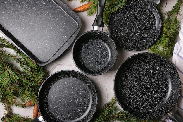 テーブルの上のクリスマスツリーと鍋とフライパンの上面図のセット。レシピ本や料理教室のコンセプト。