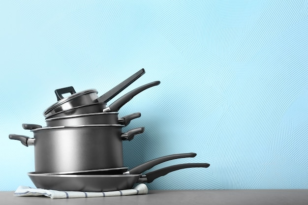 色の壁に対してテーブルの上の料理教室のために準備された鍋のセット