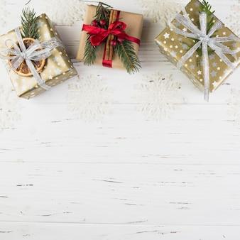 Набор настоящих коробок в рождественском обертывании между орнаментальными снежинками