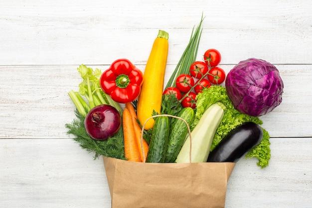 Набор продуктов в бумажном пакете на белом фоне деревянных. покупки в супермаркете или на рынке. концепция: здоровое вегетарианское питание.
