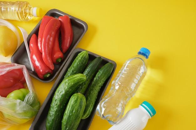 Набор продуктов в различной пластиковой упаковке, концепция загрязнения окружающей среды пластиком, скажи нет пластику, желтый фон, копия пространства, вид сверху