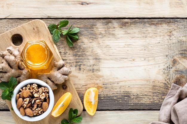 Набор продуктов для повышения иммунитета. мед, лимон, орехи, имбирь для повышения иммунитета. вид сверху. копировать пространство