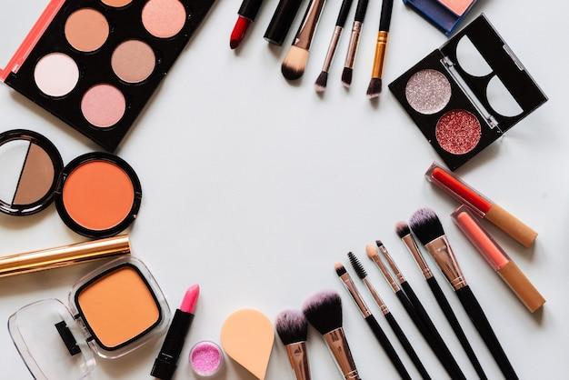 Набор профессиональной косметики: кисти для макияжа, тени, помада - изолированные на светлом фоне. вид сверху. место для вашего текста.