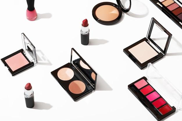 흰색 배경에 격리된 세련된 화장을 위한 전문 화장품 세트. 미용 산업 제품 상위 뷰입니다. 여성용 화장품 액세서리, 립스틱, 아이섀도, 파우더, 홍당무, 매니큐어.