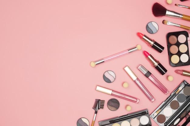 Набор профессиональной косметики, инструментов для макияжа и аксессуаров на розовом фоне, красота, мода, концепция покупок, плоская планировка. фото высокого качества