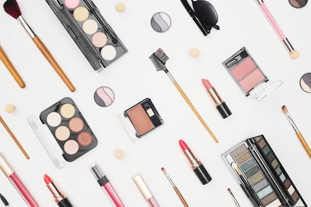 Набор профессиональной косметики, инструментов для макияжа и аксессуаров на белом фоне, красота, мода, концепция покупок, плоская планировка. фото высокого качества