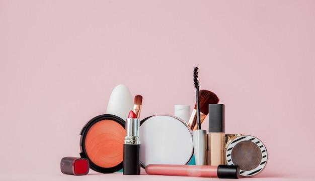 Набор профессиональной декоративной косметики, инструментов для макияжа и аксессуаров на розовой стене с копией пространства для вашего текста. понятие красоты и моды.