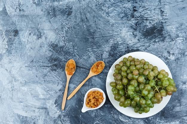 Набор изюма и зеленого винограда в белой тарелке на фоне шероховатой штукатурки. вид сверху.