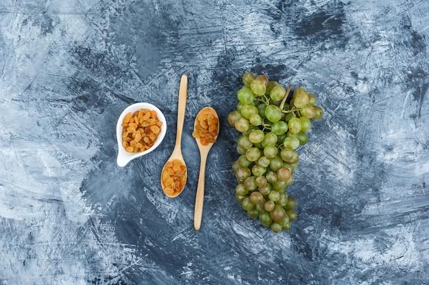 Набор изюма и зеленого винограда на фоне шероховатой штукатурки. вид сверху.