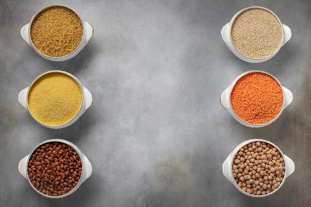 Набор пищевых рамок из сырой крупы (булгур, кускус, фасоль, лебеда, чечевица, нут), место для текста серая поверхность