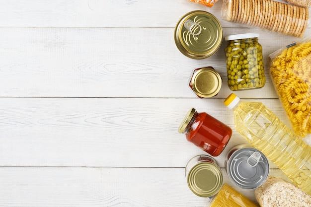 生の穀物、穀物、パスタ、白いテーブルの上の缶詰食品のセット。コピースペース。フラット横たわっていた。