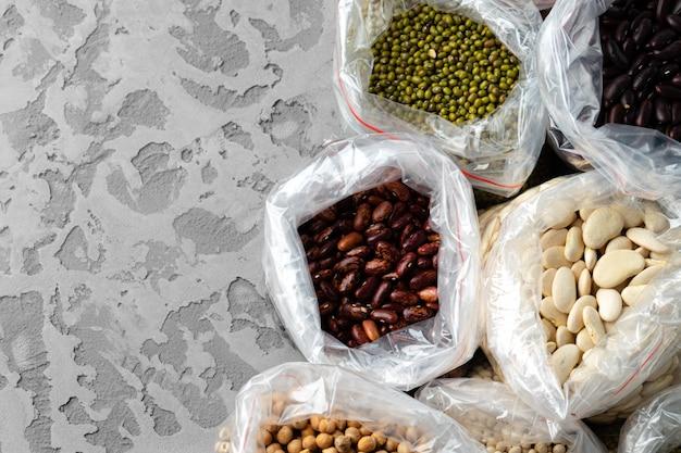 Набор сырых хлопьев, зерна, макаронных изделий и консервов на столе.