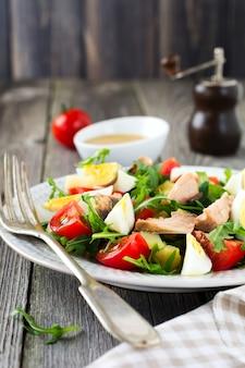 원시 재료 감자, 계란, 신선한 arugula, 올리브 오일, 후추, 통조림 참치, 체리 토마토, 소금 세트는 오래 된 나무 배경에 샐러드 니코와 즈를 준비합니다. 소박한 스타일 선택적 초점.