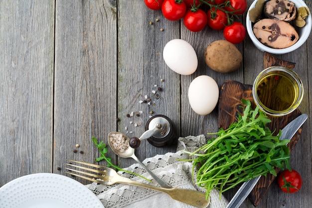 원시 재료 감자, 계란, 신선한 arugula, 올리브 오일, 후추, 통조림 참치, 체리 토마토, 소금 세트는 오래된 나무 표면에 샐러드 니코와 즈를 준비합니다