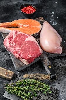 Набор сырых стейков из мяса лосося, говядины и курицы на разделочной доске. черный фон. вид сверху.