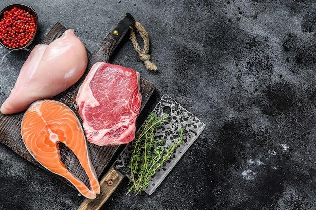 まな板に生肉ステーキサーモン、ビーフ、チキンのセット。上面図。