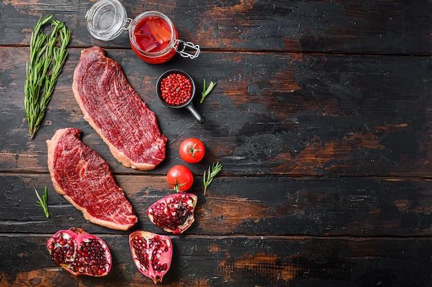 調味料、ハーブ、唐辛子、スパイシーなラー油、ザクロを添えた生のピカンハビーフステーキのセット。古いダークウッドのテーブルの上に、テキスト用のスペースがある上面図。