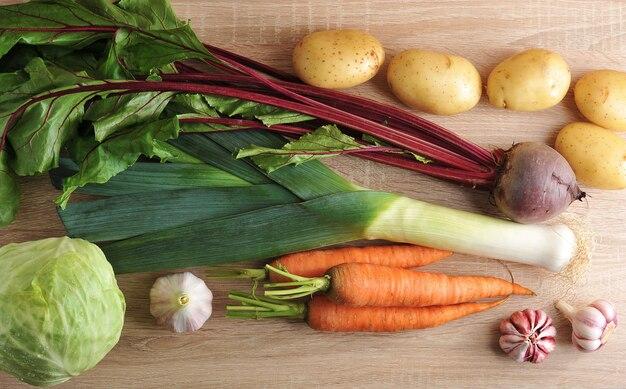 Набор сырых овощей для здорового питания, лук-порей, свекла, картофель, морковь, капуста, чеснок на деревянном фоне