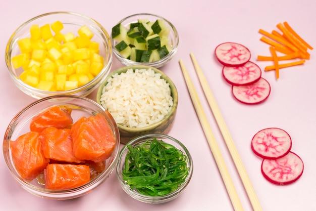 Набор сырых овощей, красной рыбы, риса, в стеклянных мисках. гавайское блюдо.