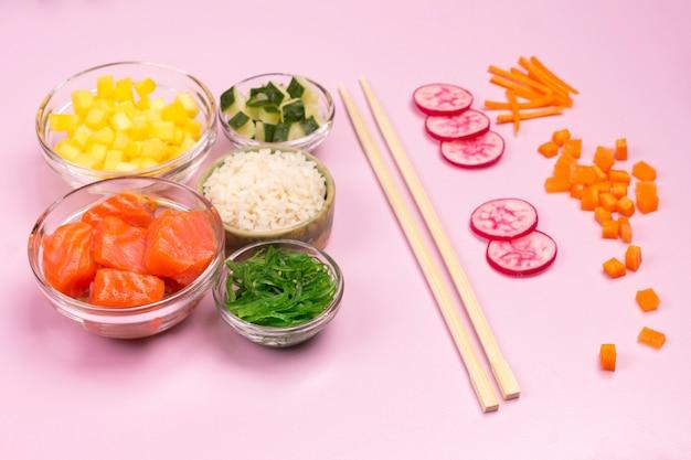 Набор сырых овощей, красной рыбы, риса, соевого соуса в стеклянных мисках. гавайское блюдо. бамбуковые палочки для еды