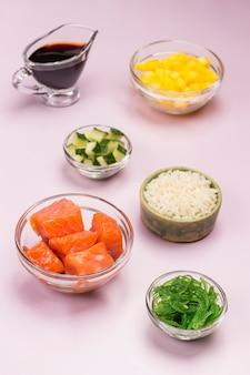 Набор сырых овощей, красной рыбы, риса, соевого соуса в стеклянных мисках.