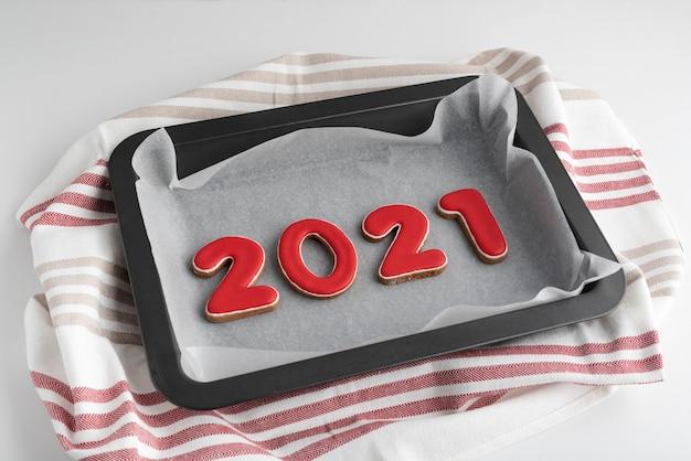 赤い数字のセット2021、ベーキングシート上のジンジャークッキー。伝統的なクリスマスのジンジャーブレッド。