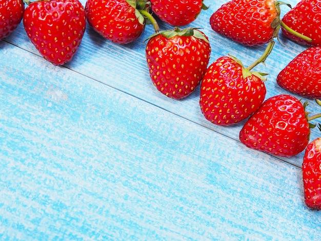 Набор красной клубники на синем деревянном фоне. сочные фрукты.