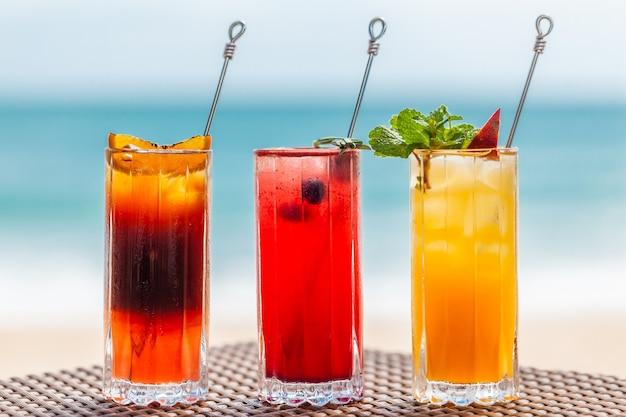 Набор освежающих фруктовых коктейлей, стоящих на столе на пляже у бирюзового моря