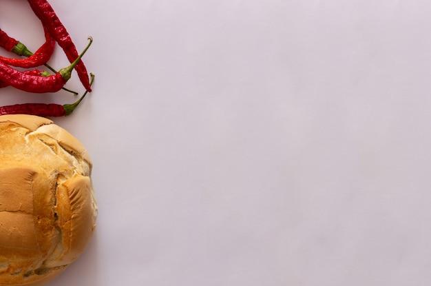白い背景の上の田舎のパンと薄い赤唐辛子のセットです。上面図。フラットレイ。スペースをコピーします。