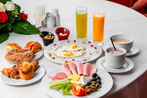 サラダ、目玉焼き、ペストリー、白い背景の上のテーブルでおいしい朝食のセット。ハイアングル。
