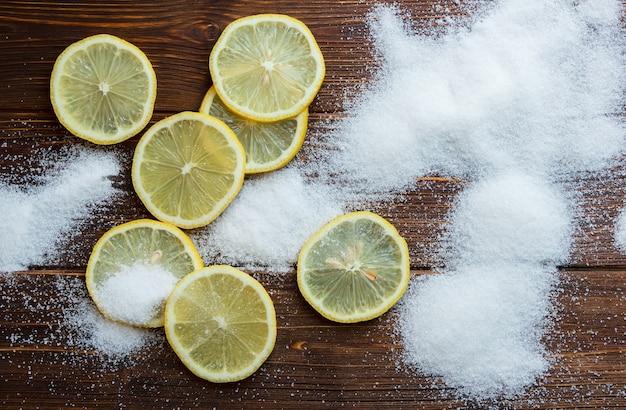 Набор соли на нем и ломтики лимона на деревянной поверхности. вид сверху. скопировать место для текста