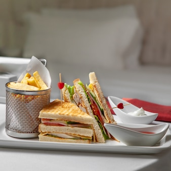 寝室の背景にサービングトレイのサンドイッチ、フライドポテトファーストフードのセット。側面図。