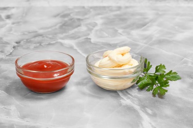 Набор соусов - стеклянные миски с кетчупом и сырным соусом с листьями петрушки на кухонном столе .. вид сверху.