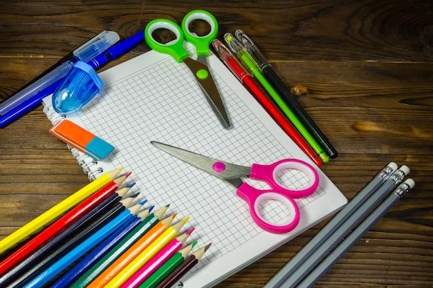 Набор школьных канцелярских принадлежностей. пустой блокнот, цветные карандаши, ручки, ножницы, ластик на деревянном столе. вернуться к школьной концепции