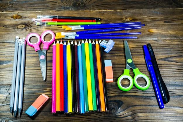 Набор школьных канцелярских принадлежностей. цветные карандаши, ручки, ножницы, ластик, кисти на деревянном столе. вернуться к школьной концепции