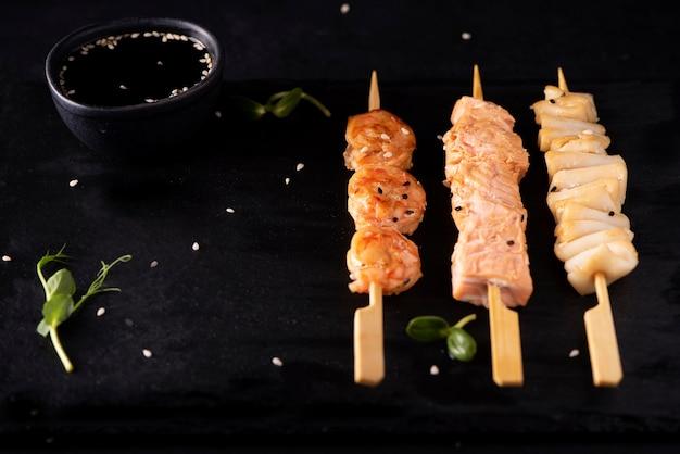 Набор кебабов из морепродуктов с соевым соусом и кунжутом на черной доске